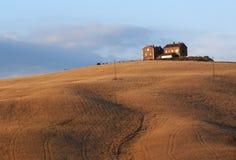 Campo di frumento e dell'azienda agricola al tramonto fotografia stock libera da diritti