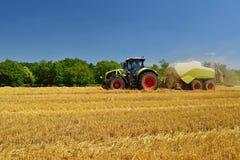 Campo di grano maturo dorato di raccolto meccanico di agricoltura della mietitrice Trattore - fieno e paglia, fondo tradizionale  Fotografia Stock