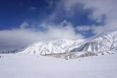 Campo di Mudoro a novembre con il fondo della montagna della neve Immagini Stock