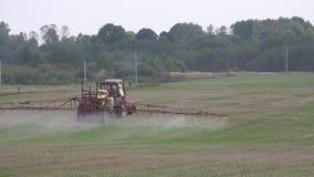 Campo di stoppie dello spruzzo del trattore con i prodotti chimici dei diserbanti in azienda agricola 4K stock footage