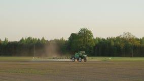 Campo do pulverizador do trator com produtos químicos para a proteção de plantas da colheita da erva daninha e da praga vídeos de arquivo