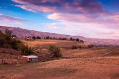 Campo e celeiro com nuvens cor-de-rosa e o céu azul Fotos de Stock