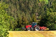 Campo e funzionamento del trattore Vento e polvere sopra i lavoratori Trattore rosso su un campo Paesaggio agricolo nel Republ ce Immagini Stock Libere da Diritti