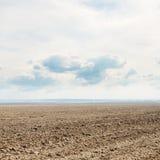 Campo e nuvens pretos da mola no céu foto de stock royalty free