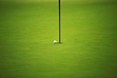 Campo e palla da golf verdi sul foro Immagini Stock Libere da Diritti