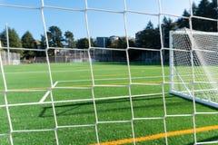 Campo e porta de futebol com um campo artificial do relvado Foco macio, bokeh Fundo do futebol fotos de stock royalty free