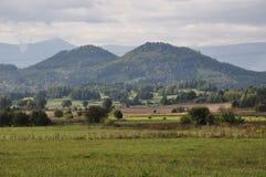Campo en las montañas del fondo fotografía de archivo
