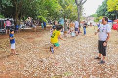 Kids playing, jumping rope like the old days. Campo Grande, Brazil - July 08, 2018: People on public square enjoying the sunday on the Praça Bolivia event. Kids stock photos