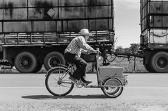 Old man riding a old bicycle selling ice creams on a highway. Campo Grande, Brazil - May 24, 2018: Old man riding a old bicycle selling ice creams on a highway Royalty Free Stock Photo