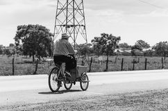 Old man riding a old bicycle selling ice creams on a highway. Campo Grande, Brazil - May 24, 2018: Old man riding a old bicycle selling ice creams on a highway Stock Photo