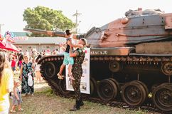 Soldier holding a boy with a war tank behind. Campo Grande, Brazil - September 09, 2018: Soldier holding a boy with a war tank behind to take a photo at the royalty free stock images