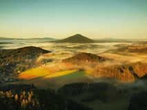 Campo hermoso del parque de Checo-Sajonia Suiza Niebla apacible sobre iglesia del pueblo Los rayos calientes del sol luchan con l Fotografía de archivo libre de regalías