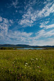 Campo, lago y montañas verdes Fotografía de archivo