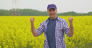 Campo masculino feliz da colza de Celebrating Success At do fazendeiro vídeos de arquivo