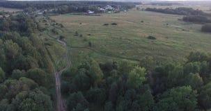 Campo nal di volo, strada verde dei prati Camion blu che guida al villaggio Tende turistiche dal lago Foresta di fioritura stock footage