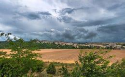 Campo perto de uma exploração agrícola sob rochas Foto de Stock Royalty Free