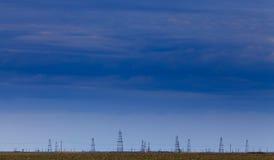 Campo petrolífero com as bombas e as plataformas petrolíferas de óleo perfiladas no céu azul foto de stock