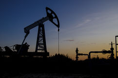 Campo petrolífero durante puesta del sol Foto de archivo libre de regalías