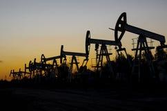 Campo petrolífero durante puesta del sol fotos de archivo libres de regalías