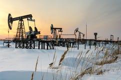 Campo petrolífero durante puesta del sol en invierno Fotografía de archivo libre de regalías