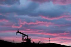 Campo petrolífero explotado en puesta del sol Imágenes de archivo libres de regalías