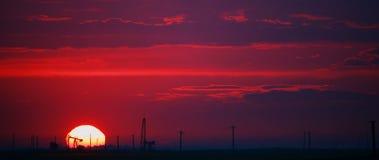 Campo petrolífero perfilado en disco solar en la puesta del sol Foto de archivo