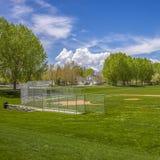 Campo quadrado do basebol ou de softball contra árvores luxúrias e construções sob o céu nebuloso imagens de stock royalty free