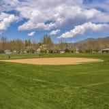 Campo quadrado do basebol ou de softball do quadro com construções e árvores além do terreno gramíneo fotografia de stock royalty free