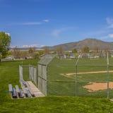 Campo quadrado do softball ou de basebol com vista da montanha e do céu em um dia ensolarado imagem de stock