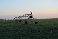 Campo que es irrigado en la puesta del sol Fotos de archivo libres de regalías