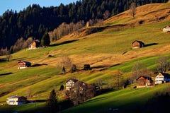 Campo que vive en paisaje alpino de la puesta del sol de las colinas Fotos de archivo libres de regalías