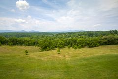 Campo recentemente segado com forst e montanhas distantes no fundo sob o céu azul brilhante imagens de stock royalty free