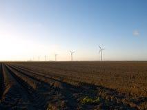 Campo recientemente arado con las turbinas de viento en la puesta del sol Imagenes de archivo