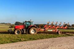Campo rosso del palo del trattore Lavoro di campo di autunno Vita sull'azienda agricola Paesaggio agricolo in repubblica Ceca Fotografie Stock Libere da Diritti