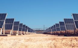 Campo solar com estação da energia elétrica no fundo fotos de stock
