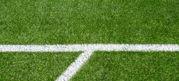 Campo sportivo artificiale sintetico verde di calcio dell'erba con la linea d'angolo bianca della banda fotografie stock