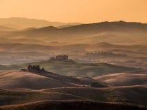 Campo toscano con las colinas y las granjas Fotografía de archivo libre de regalías
