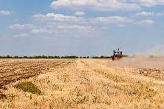 Campo, trattore, cielo blu e nuvole di falciatura Fotografia Stock