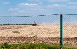 Campo, trattore, cielo blu e nuvole di falciatura Fotografie Stock Libere da Diritti