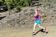 Campo a través de la mujer que corre en montañas imagen de archivo