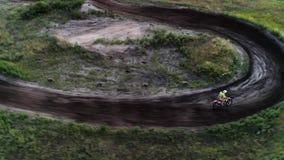 Campo a través de la pista del piloto de carreras del motocrós que circunda almacen de metraje de vídeo
