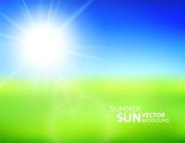 Campo verde borroso y cielo azul con el sol del verano Foto de archivo libre de regalías