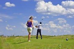 Campo verde e céu azul nebuloso, jogadores de golfe Fotos de Stock Royalty Free