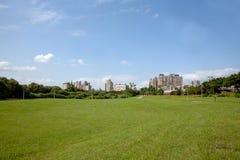 Campo verde e a cidade Foto de Stock Royalty Free