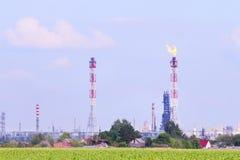 Campo verde e grande raffineria di petrolio con i tubi Immagini Stock