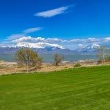 Campo verde luxúria do quadrado do quadro na frente de um lago com a costa gramínea vista em um dia ensolarado fotos de stock