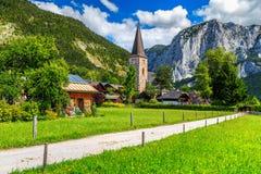 Campo verde sbalorditivo e villaggio alpino con le montagne, Altaussee, Austria Fotografie Stock