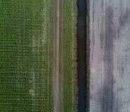 Campo verde y campo de la suciedad separado por pequeño cannal del agua Fotografía de archivo libre de regalías