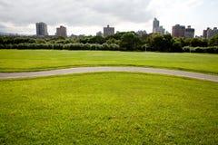Campo verde y la ciudad Fotos de archivo libres de regalías