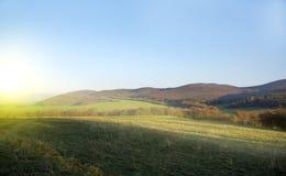 Campo y cielo verdes con resplandor de la mañana Montaña en la parte posterior imágenes de archivo libres de regalías